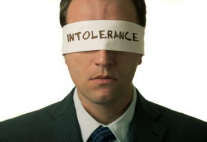 "Blindfolded man with ""intolerance"" text on the blindfold"