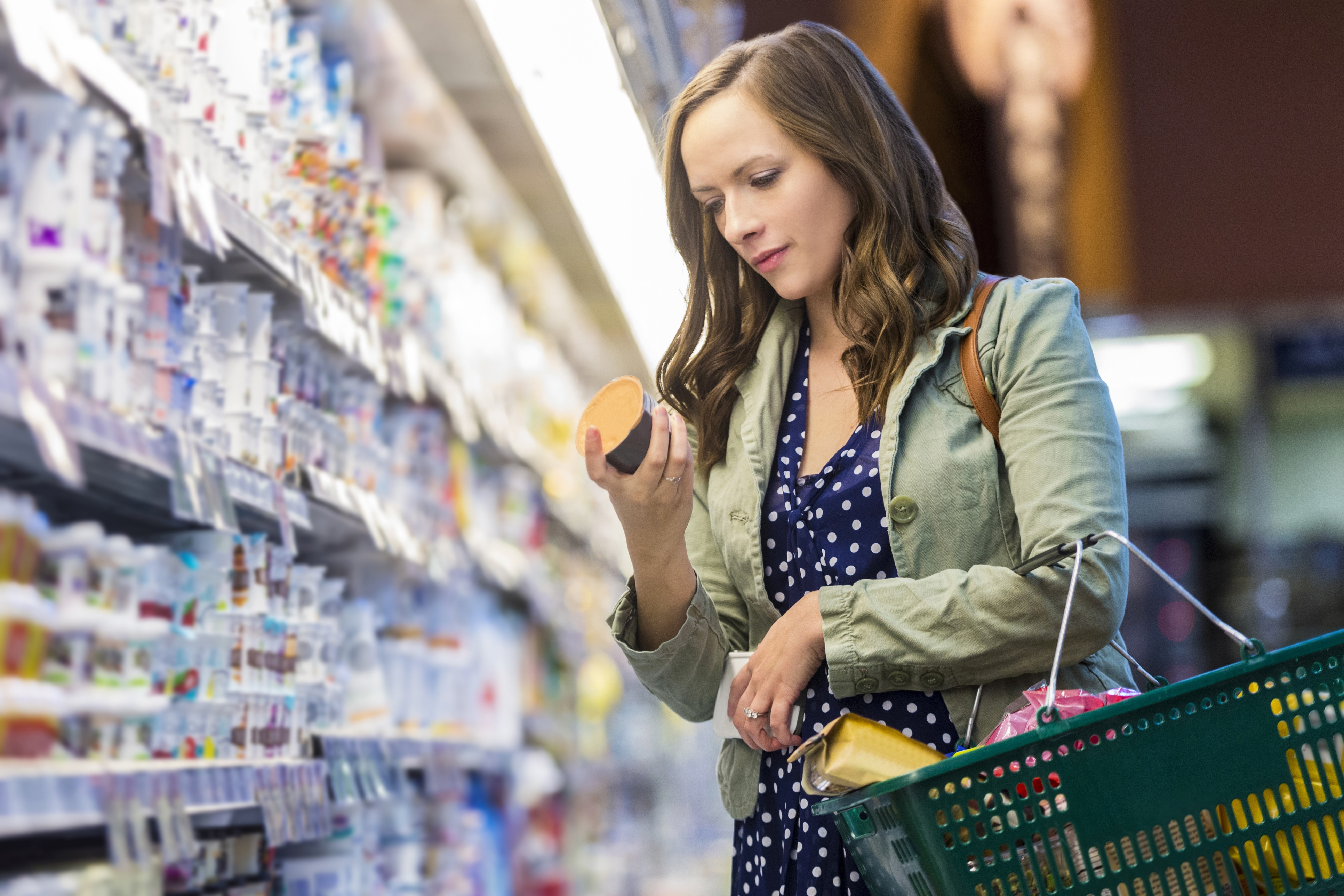 Woman reading food labels at grocery store