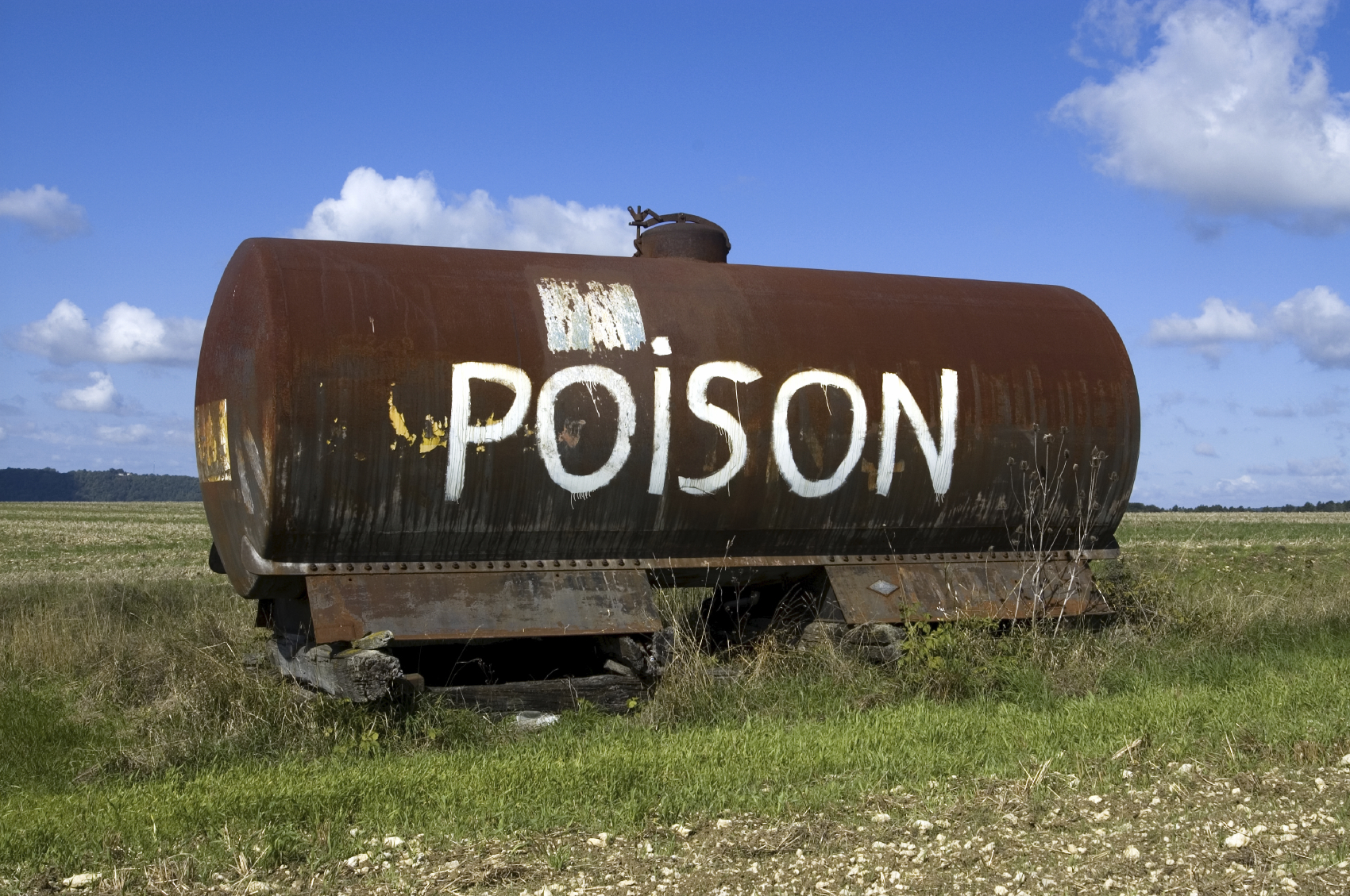 Poison painted on container in field