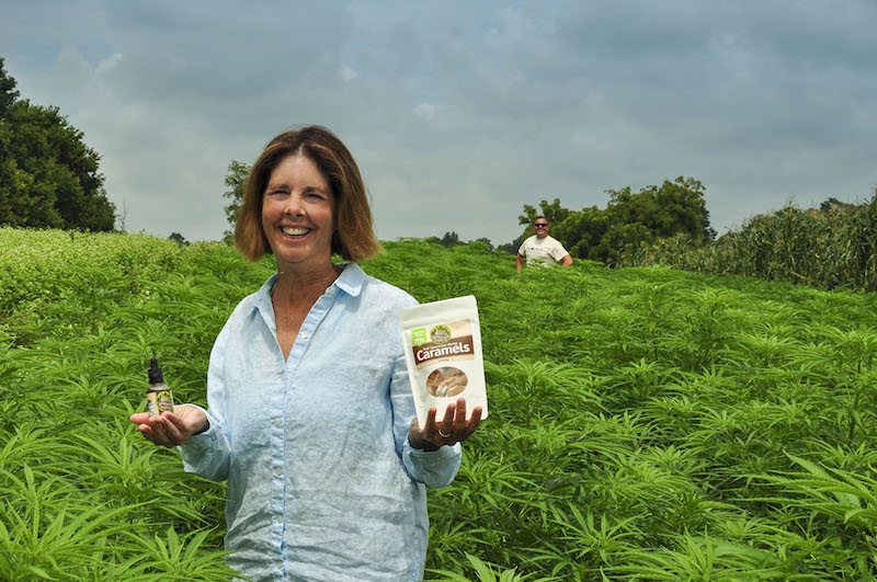 Laura Freeman, owner of Mt. Folly Farm in Kentucky, shows hemp derived products standing in a field of hemp