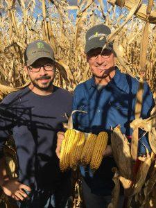 Photo of 2 men showing corn